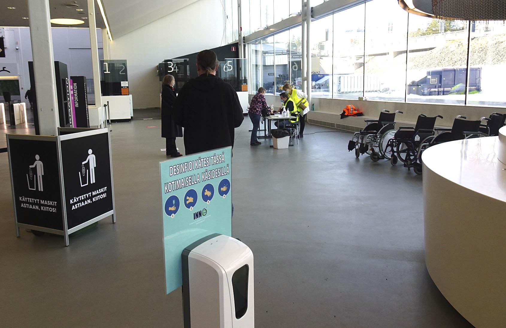 Kolme ihmistä jonottaa turvavälein koronarokotuksen ilmoittautumispisteeseen avarassa aulassa. Etualalla käsidesiautomaatti ja roskakori käytetyille hengityssuojaimille.