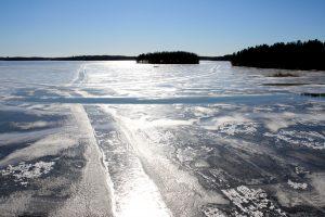 Aurinko kimmeltää järven jäästä.