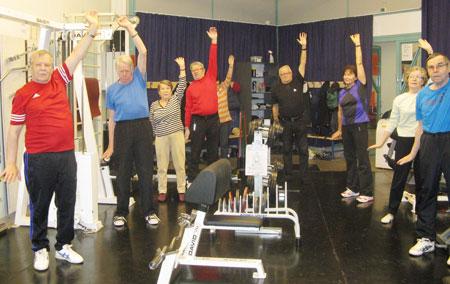 Pässijumppaa kuntosalilla alkuverryttelynä. Jumppa-maikkana toimii Kauko Niemelä (alempi kuva oikealla), Kuntorannan kurssin käynyt.