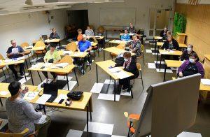 Kurssilaisia istumassa työpöytiensä takana opetustilassa.