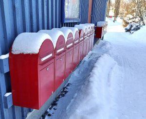 Punaisia postilaatikoita rivissä ulkorakennuksen seinustalla.