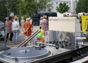 Etualalla tiskijukan levysiitin ulkoilmatapahtumassa, taustalla ryhmä kesäisesti pukeutuneita ihmisiä seuraamassa kulttuuritapahtumaa.