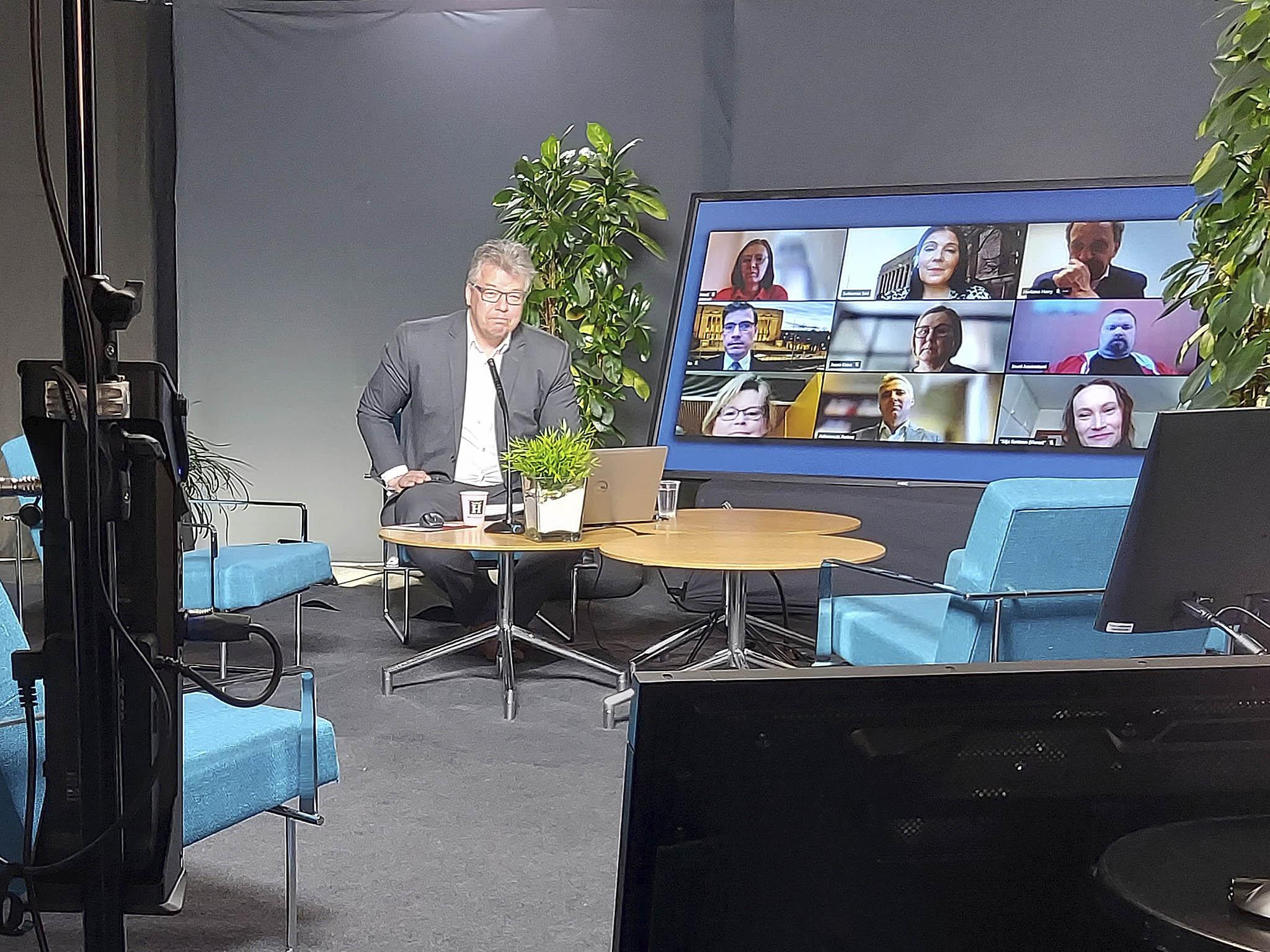 Paneelin juontaja Jussi Kärki istuu tv-studion tuolilla, isolla näytöllä hänen vieressään näkyvät yhdeksän eduskuntapuolueen edustajat, kukin omassa pienessä ruutukuvassaan.